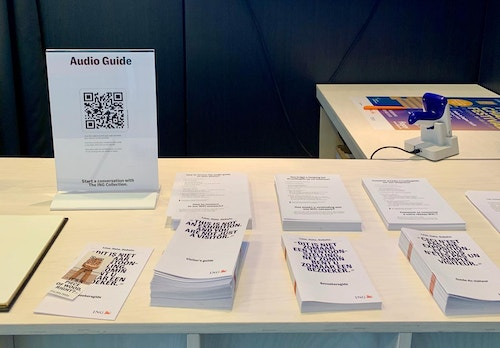 The audio guide is promoted through the visitor guide, ticket slip, and on screens behind the welcome desk.