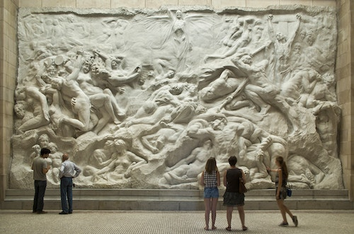 Visitors standing in front of a mural sculpture in the Art and History Museum in Brussels