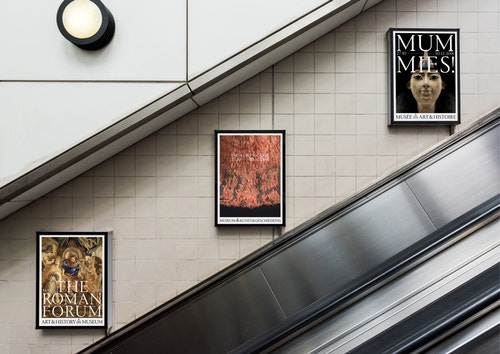 Posters promoting the exhibitions of the Art and History Museum hanging above an escalator