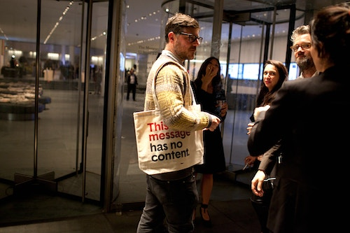 """A man entering the room of the event """"Base At Moma"""" with a tote bag designed by Base"""