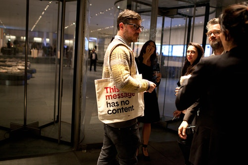"A man entering the room of the event ""Base At Moma"" with a tote bag designed by Base"