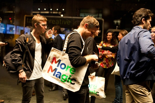 Several young men during the meet-up with tote bags designed by Base
