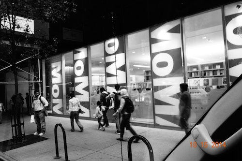 Facade of the Moma by night with people walking by