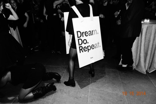 "A woman with a sign designed by Base quoting ""Dream, do, repeat."""