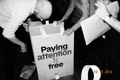 "Two people fiwing a sign with the quote ""Paying attention is free"""