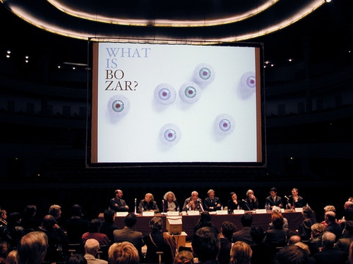 """Poster """"What is Bozar?"""" displayed on a screen during a conference"""