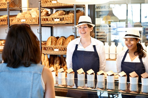 Two bakers greeting a customer in a bakery