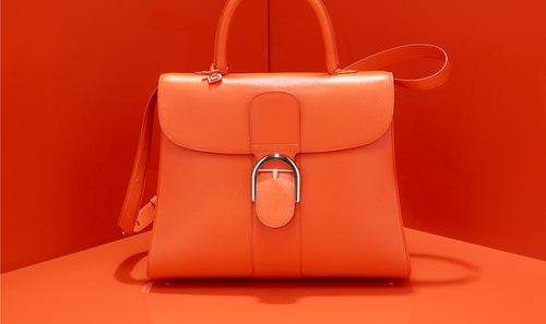 Delvaux brillant Mini Satchel bag on an orange background