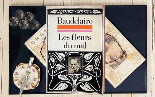 "A stylish book cover of Baudelaire's work ""Les fleurs du mal"" on a table"