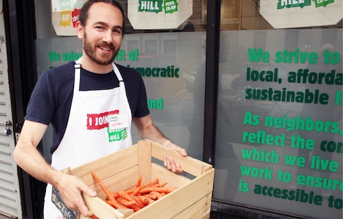 Greene Hill team member holding a box of organic food