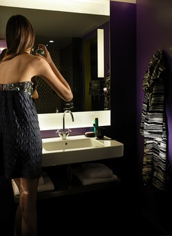 A girl putting perfume in front of a mirror in a bathroom of the Hotel Missoni