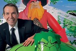 Jeff Koons pausing with a Hulk mascot
