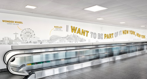 A wall illustration of New York with a quote next to an escalator