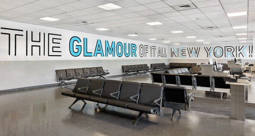 "A signage in a waiting room of Jfk Terminal 4 saying ""The glamour of it all New York!"""