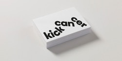Pile of business cards designed for KickCancer on a table