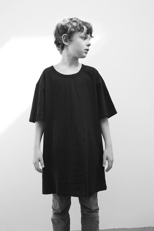 A young boy wearing an oversized t-shirt