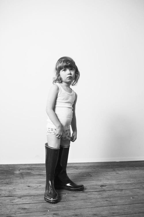 A little girl wearing oversized boots