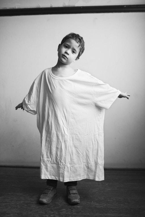 A little boy wearing an oversized t-shirt
