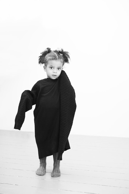 A little girl wearing an oversized sweater