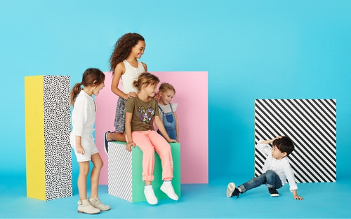 Children posing next to blocks of colours in a studio