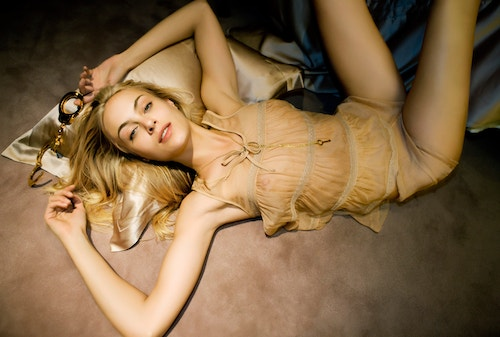 A blond girl laying on the ground with Kiki De Montparnasse lingerie products