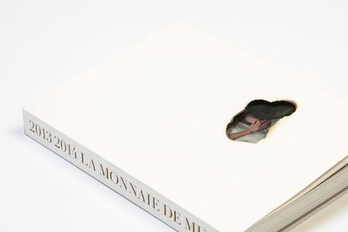 A brochure designed for La Monnaie de Munt on a white table