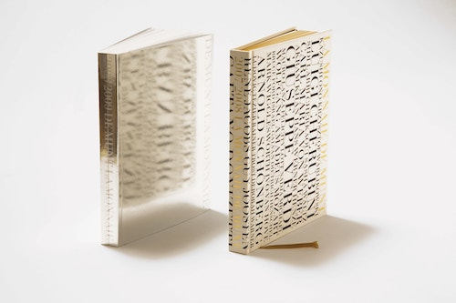 Two glossy paper brochures designed for La Monnaie De Munt standing on a white table