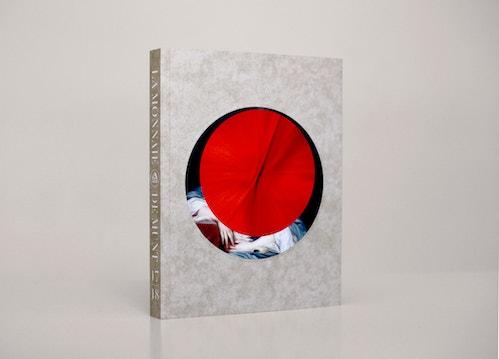 A brochure designed for La Monnaie De Munt standing on a beige table