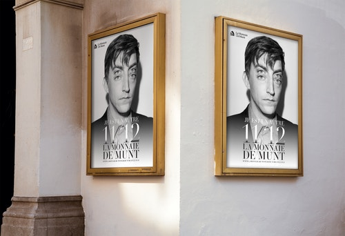 Two posters designed for La Monnaie De Munt in golden frames hanging on a wall