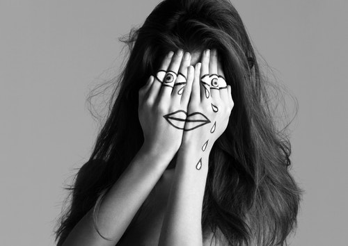 A girl hiding her face with her hands on which there is an illustration of a crying face