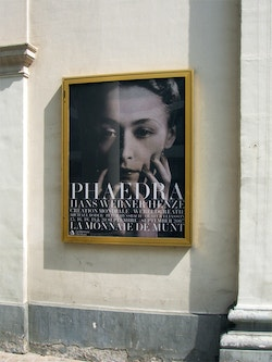 A poster designed for the Phaedra show at La Monnaie De Munt hanging on a wall
