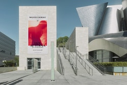 A poster designed for Los Angeles Master Chorale's anniversary displayed on an infrastructure next the building of Los Angeles Master Chorale