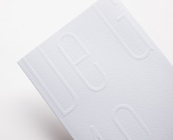Close-up view of the embossing text on the brand book designed for Maison de Greef