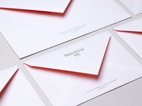 A set of different sizes enveloppes designed for Maison de Greef on a table