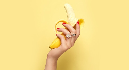 A hand with red nail polish wearing Maison de Greef rings holding a banana in front of a yellow background