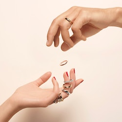 A hand tossing a Maison De Greef ring on top of another hand receiving it, in front of a peach background