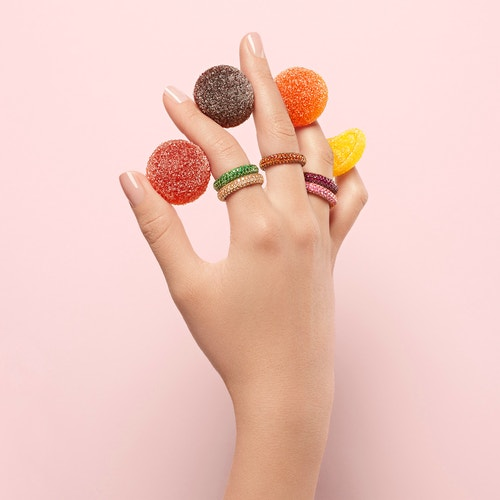 A hand with rings from Maison De Greef holding colorful candies between each finger, in front of a pale pink background