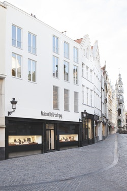 View of the street with the store of Maison De Greef by day