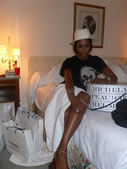 Naomi sitting next to a Maison Michel hat box in her hotel room