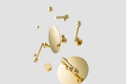 The different components of a golden doorknob from Maison Vervloet flying in the air