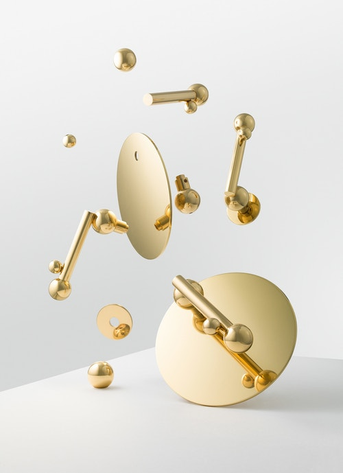 The different components of a golden doorknob flying in the air
