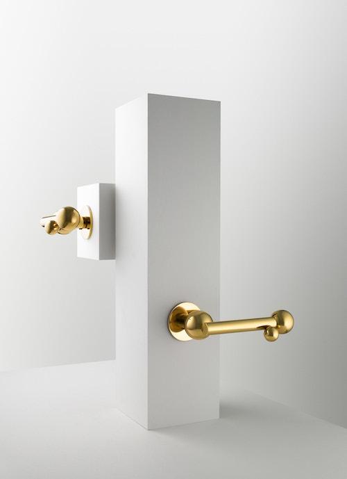 Two golden doorknobs from Maison Vervloet on white blocs