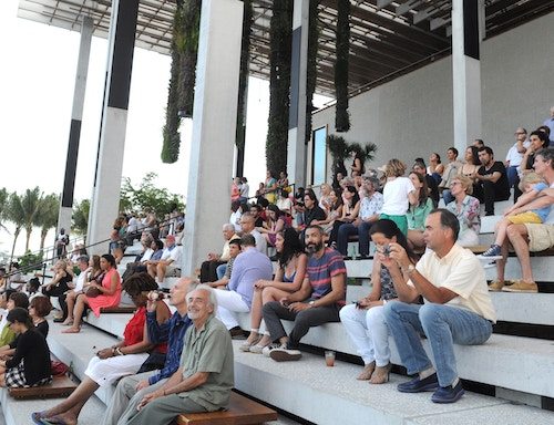 An audience sitting outside at the Miami Art Museum