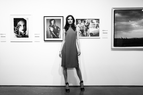 A model pausing in front of a wall with artworks hanging