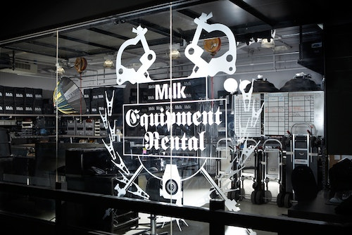 A window of an equipment rental workshop branded with the Milk logo