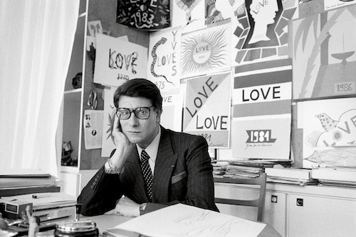 Yves Saint-Laurent sitting at his desk in his office