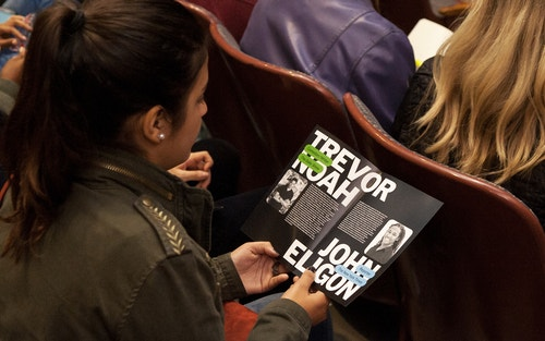A girl sitting at a conference reading the brochure of the program