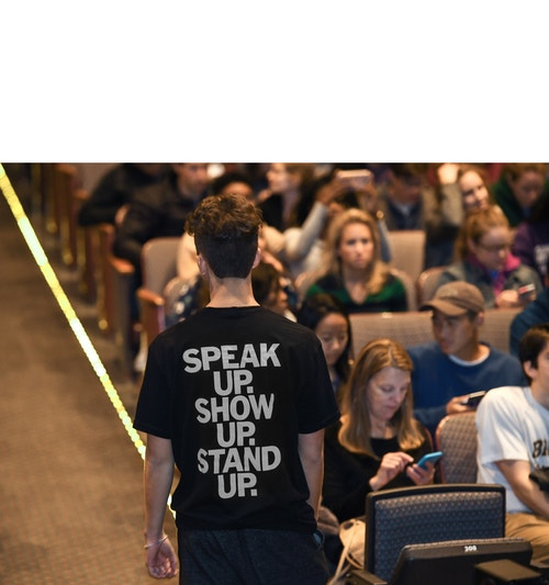 A man wearing a t-shirt branded for the New York Times' conferences