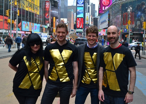 People in Times Square wearing a t-shirt designed with the NYC x Design logo