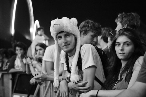 A guy in the middle of a crowd wearing an animal hat